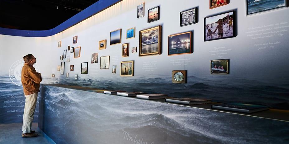 Näyttelyvieras tutkii kuvassa seinälle kehystettyjä tauluja ja niiden alle kirjoitettuja itämerimuistoja.
