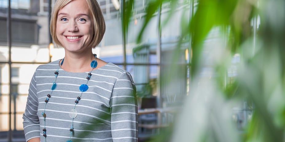 Spondan vastuullisuuspäällikkö Pirkko Airaksinen kuvattu sisätiloissa vihreän kasvin katveessa.